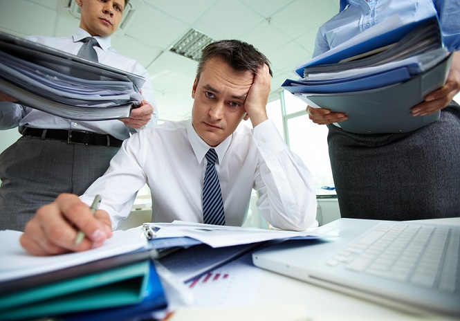 Close up of over-worked man in office surrounded by papers