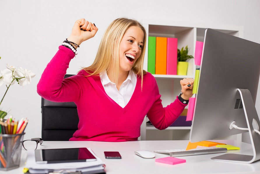 Happy business woman in office sitting by laptop