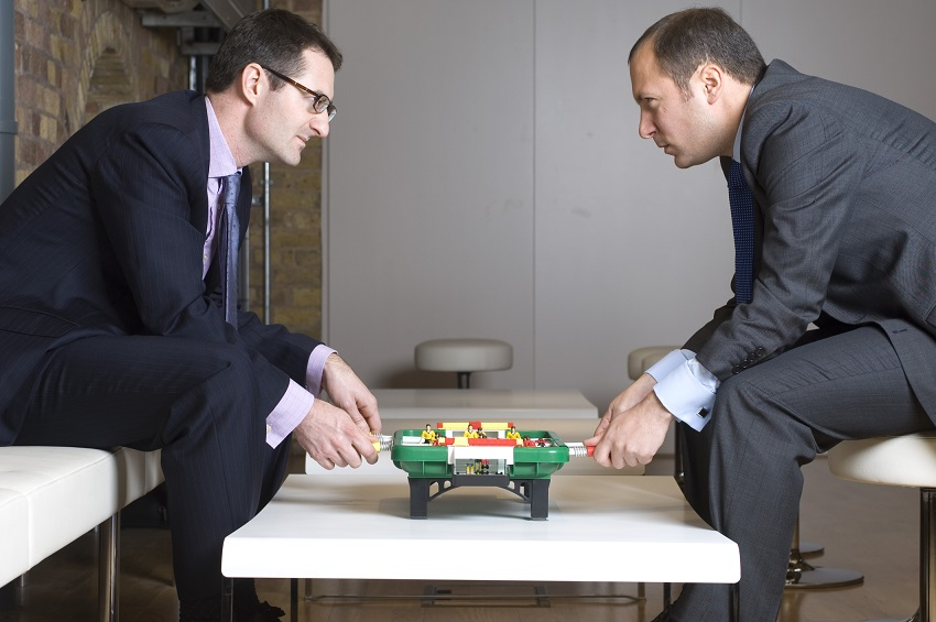 Two businessmen playing foosball