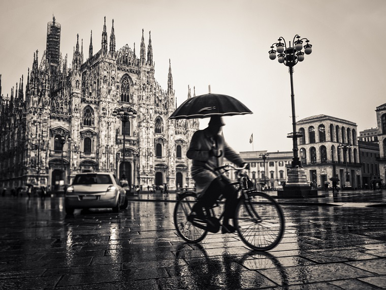 Businessman riding a bike in the rain with an umbrella