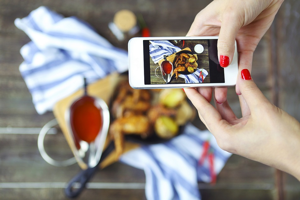 Woman taking a photo of a hot meat dishes on the wooden background with smartphone. Grilled chicken wings with red spicy sauce