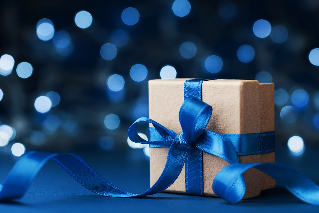 Holiday gift box or present with bow ribbon against blue bokeh background. Magic christmas greeting card. Copy space for data or design
