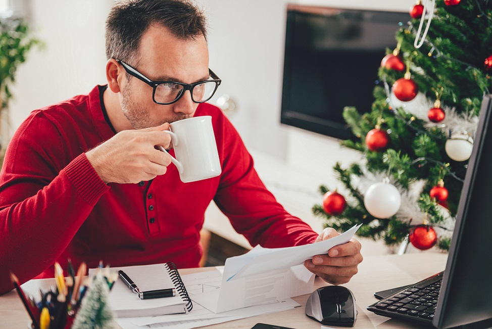 Man wearing red sweater reading letter and drinking coffee with a christmas tree in the background