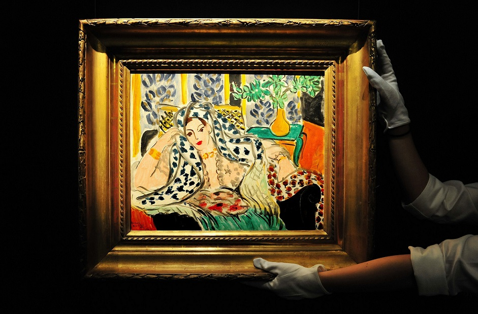 Sotheby's gallery assistant Freddi Privite adjusts Odalisque Au Fauteuil Noir by Henri Matisse, with an estimate between £9-12 million, ahead of the auction house's forthcoming auction