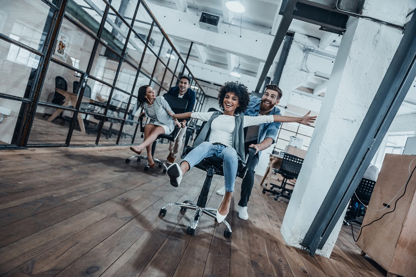 Four young cheerful business people in smart casual wear having fun while racing on office chairs and smiling