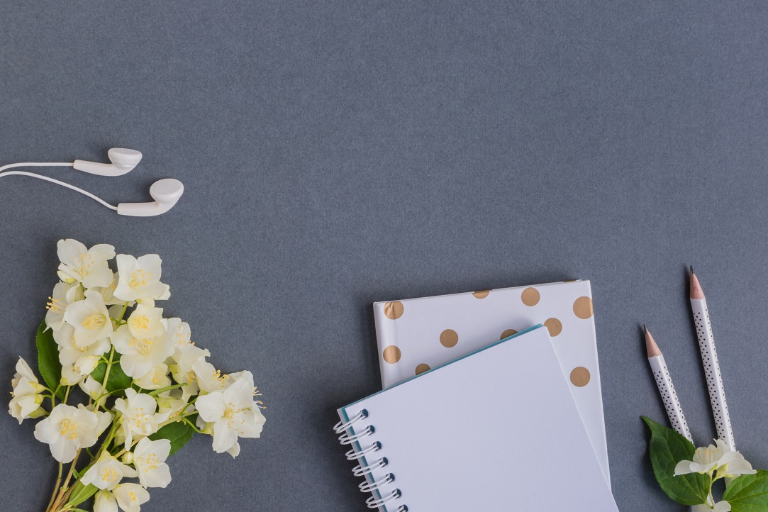 Flat lay desk with white jasmine flowers and notebook on dark background