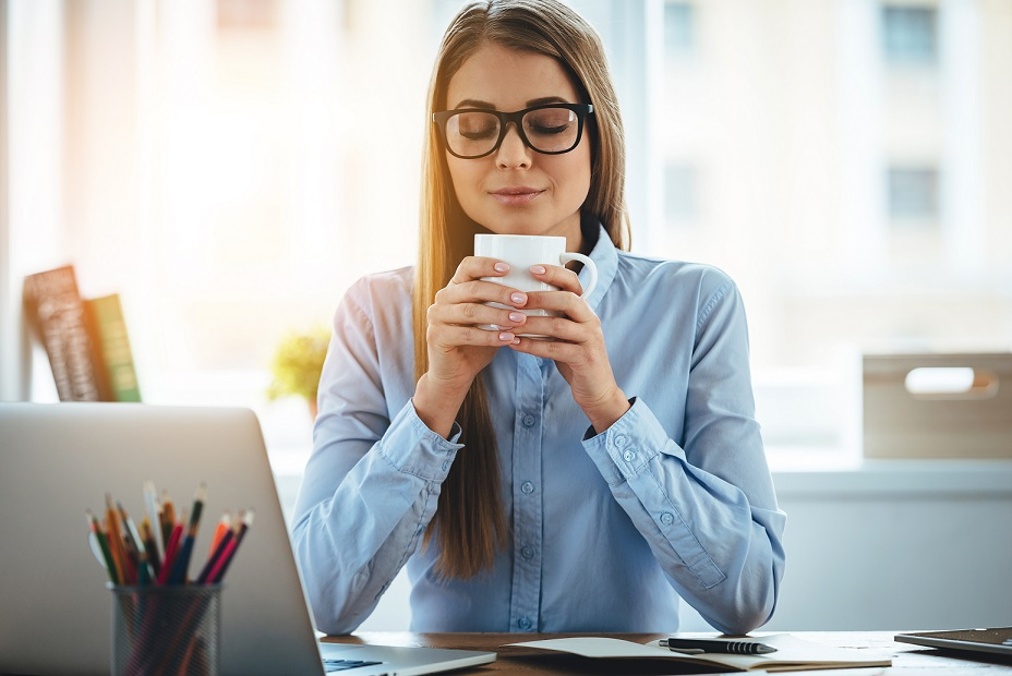 Young beautiful woman holding coffee cup and keeping eyes closed while sitting at her working place