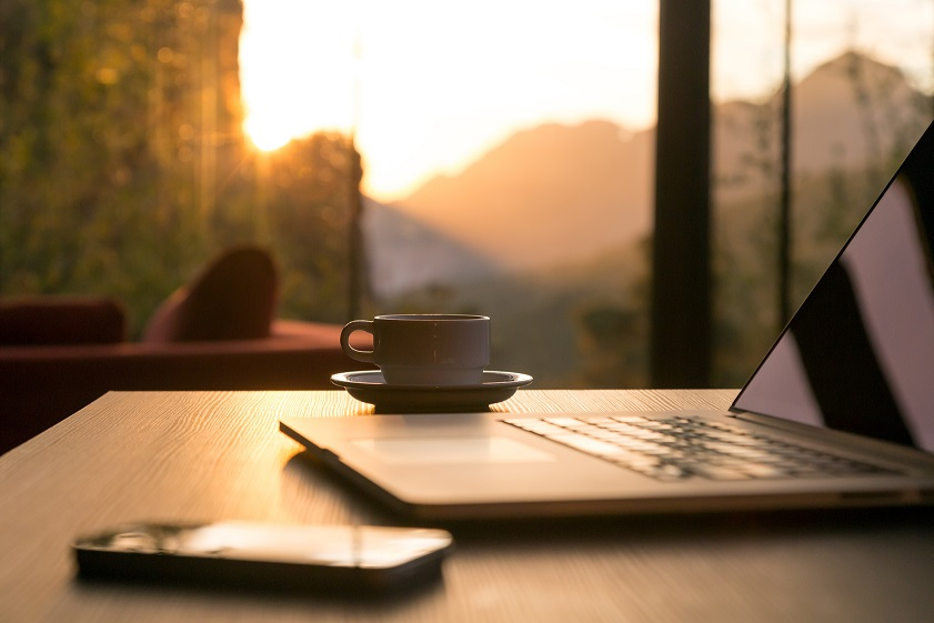 Nomad work Concept Image Computer Coffee Mug and Telephone large windows and sun rising, focus on coffee mug