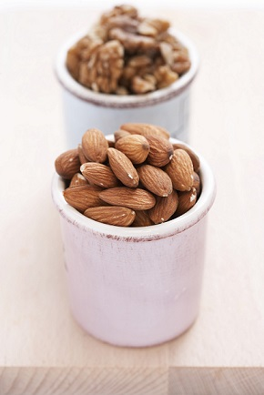 Almonds and walnuts in containers, close-up