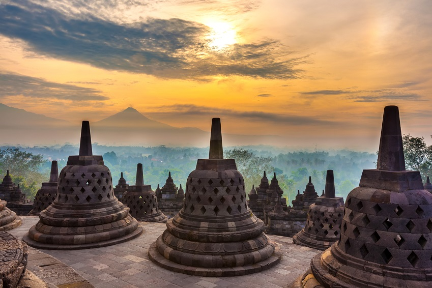 Taman Lumbini park from the height of the temple complex Candi Borobudur at sunrise in the fog.