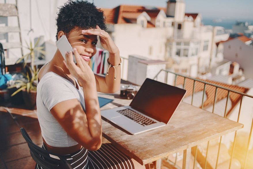 Young remote worker shielding her yese from the sun